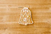 Bell-shaped gingerbread, decorated with icing and sprinkling, on a light wood texture background.