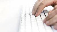 a male hand over the white keyboard of a computer before typing