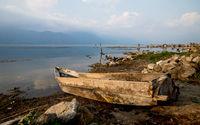 Local wooden fishermen boat at the coast along lake Atitlan during sunset in San Pedro la Laguna, Guatemala