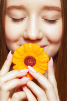 Teenager girl with  flower lollipop in hands closing mouth and smiling.