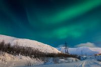 Northern Lights over snow capped hills.