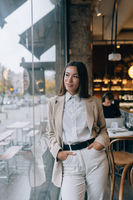 Young woman standing in front of windows in cafe.