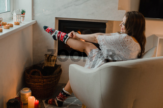 the beautiful woman is chilling at home near fireplace