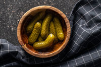 Small pickles. Marinated pickled cucumbers in wooden bowl.