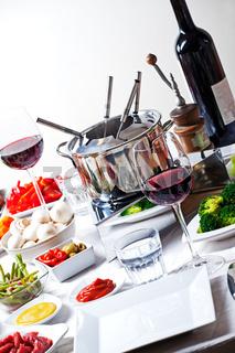 Tisch mit Fondueset und Zutaten
