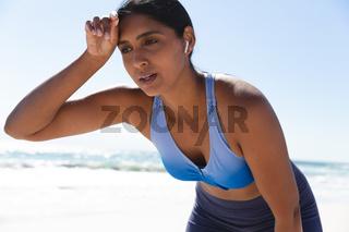 Mixed race woman exercising on beach wearing wireless earphones taking rest