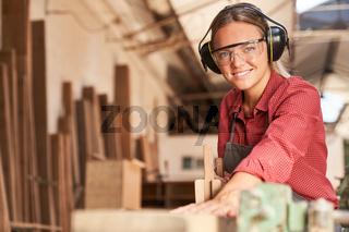 Junge Frau als Handwerker Lehrling mit Gehörschutz