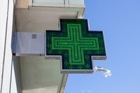 Pharmacy electric sign on building facade. Illuminated Green cross