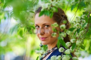 Beautiful woman among blossoming trees
