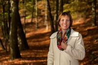 Lächelnde Frau mit einem Herbstwald im HIntergrund
