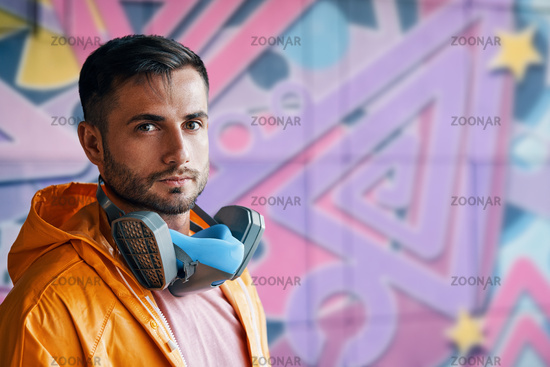 Portrait of handsome street artist staying on his graffiti painting background