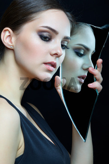 Young female with eyes closed and mirror shard in hands.