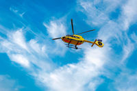 Paramedic rescue helicopter against blue cloud sky. Starting helicopter, flying ambulances