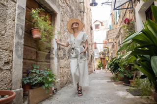 Beautiful blonde young female traveler wearing straw sun hat sightseeing and enjoying summer vacation in an old traditional costal town at Adriatic cost, Croatia.