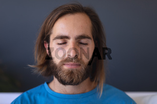 Caucasian man sitting on sofa meditating with eyes closed