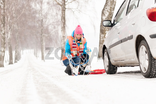 Woman with tire chains car snow breakdown