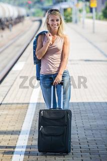 Frau mit Koffer am Bahnsteig
