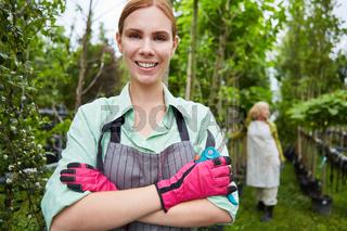 Junge Frau als stolzer Gärtner Azubi mit Gartenschere