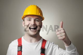 Smiling young repairman with yellow hard hat