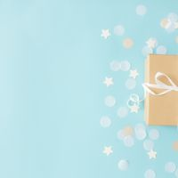 Paper gift box tied with ribbon, star and circle paper confetti or glitters