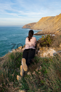 Woman on a pink shirt looking at the landscape of Cabo Espichel Cape sea cliffs and atlantic ocean, in Portugal