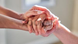 Hände halten von Seniorin für Beistand im Hospiz