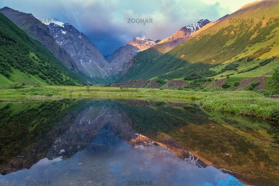 Illuminated mountains reflection in lake