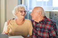 Glückliches Rentner Paar umarmt sich voller Liebe zu Hause