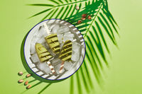 Frozen homemade pistachio popsicle in bowl of ice on green background with palm leaf shadow in harsh light. Refreshing popsicle, frozen green juice on stick. Top view, copy space
