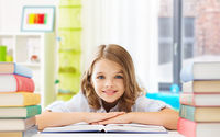 smiling student girl with books learning at home