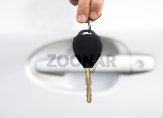 hand holding car key before door of car