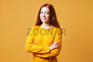 happy confident young woman with her arms folded smiling into camera