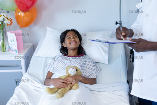 African american male doctor writing at hospital bedside of smiling sick mixed race girl