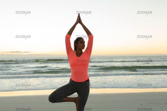 Mixed race woman on beach practicing yoga at sunset