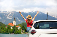 Summer vacation car road trip freedom concept. Happy woman cheering joyfuly by rising hands to the sky enjoying beautiful view of lake Bled, Slovenia, Europe.