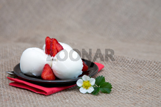 Ice cream with strawberry on black plate.
