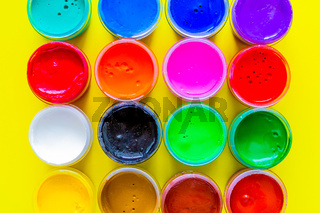 Many bright cans of paint stand together on a yellow background close-up.