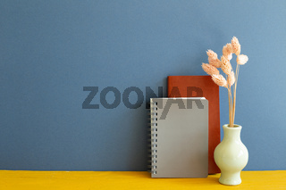 Notebook with dry flowers on yellow wooden desk. blue wall background. copy space
