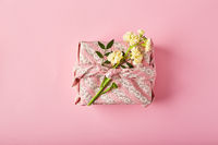 Bouquet of yellow matthiola with gift wrap in traditional japanese furoshiki style. Design concept of holiday greeting on pink table