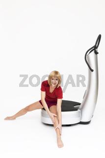 Junge Frau sitzt auf Powerplate