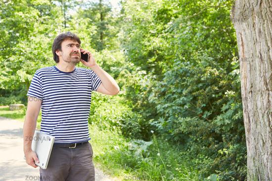 Freiberufler telefoniert mit dem Smartphone im Garten