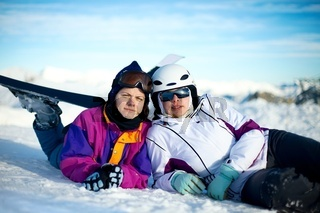 Young female skiers relaxing in the snow