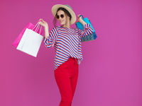 Young woman with shopping bags on pink background