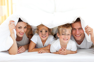 Young family playing together on a bed