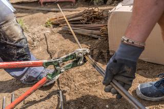 Bauarbeiter arbeitet auf Baustelle mit Bolzenschneider