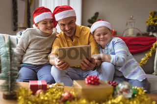 Caucasian father and two sons having a video call on digital tablet at home during christmas