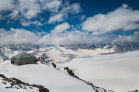 Mountain clouds over beautiful snow-capped peaks of mountains and glaciers. View at the snowy mountains.