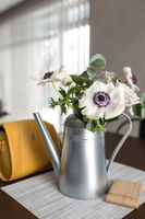 Delicate anemones flowers in metal pot vase with yellow hand bag on the table