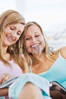 Laughingl friends reading a book