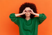 Funny woman with Afro hairstyle wearing sweater looking through fingers in binoculars gesture, observing distant with attentive look, watching afar.